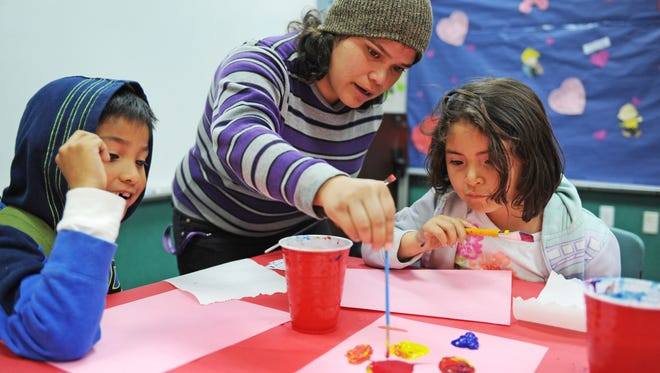 Instructor Liz Ruvalcaba works with first and second graders at the Alisal Family Resource Center's new after-school art classes. Ruvalcaba is part of the Semillas Project in Salinas.