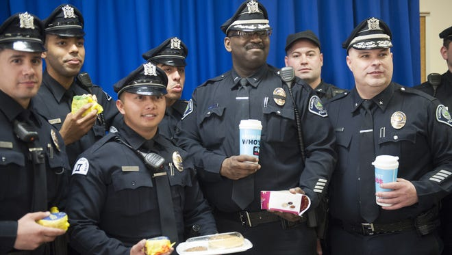 McDonald's officials surprised Camden County Police Department Lt. Zsakhiem James (center) and presented him Friday with a $500 donation to the Ronald McDonald House in Camden and free breakfast for him and other officers. McDonald's has chosen to recognize Lt. Zsakhiem James, and his recently passed K-9 partner Zero