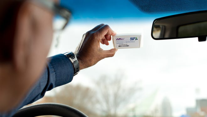 A driver holds up a RiverLink transponder to a car's windshield.