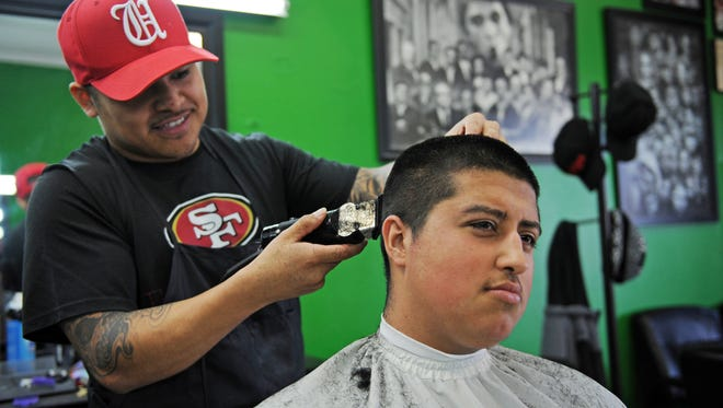 "Junior Maravilla is getting a ""taper with a lineup"" from Brian Rodriguez at Headquarters Barbershop on N. Main St. in Salinas."
