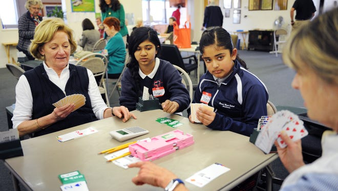 Bridge partners Celeste Falor, left, and Martha Hawley, right, talk about their game with Sacred Heart students Foran Shah and Jasmine Walia, with cards.
