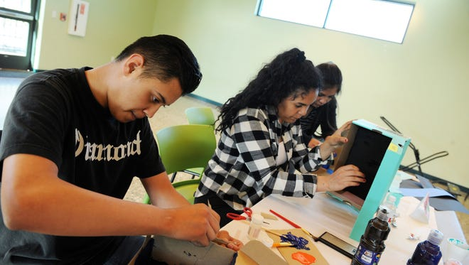 From left, Christian Gutierrez, Maria Betancourt, and Jackie Vazquez begin work on miniature altars traditionally used to honor family members during Day of the Dead. The students are participating in a YES session, a community-level violence prevention program held at the CŽésar Ch‡ávez Library in Salinas.