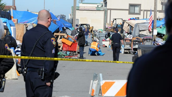 Under police guard on roped-off streets, workers hired by the city of Salinas clean out homeless encampments in the Market Way area of Chinatown.