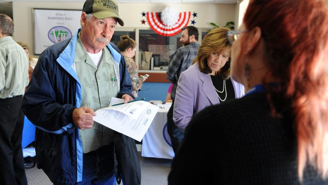 Veteran Charles Pokovich speaks with a potential employer at Tuesday's job fair hosted by the Veterans Transition Center at Martinez Hall in Marina.