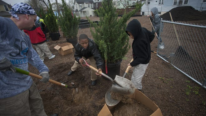 T&M Associates volunteer Ryan Leff, left, helps dig a hole to plant trees with Promise Charter School students Jameire Boggs, center, and Daniel Medero Tuesday in Camden, across the street from the school. The work is part of a new community garden project of the Camden Charter School Network. On Wednesday and Thursday, Campbell Soup Co. will help plant more trees.