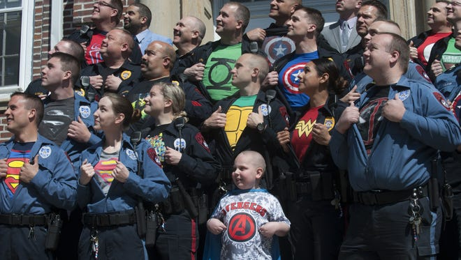 Mount Holly officers  show off their superhero shirts  in honor of 7-year-old 'Superhero' Darien Hoefling, who underwent surgery to remove a life-threatening brain tumor.
