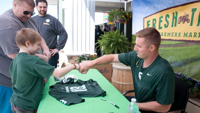 Former MSU quarterback Connor Cook fist bumps Haslett resident Dominic Knapp, 10, while signing autographs on Saturday, April 23, 2016 outside Fresh Thyme Farmers Market in East Lansing.