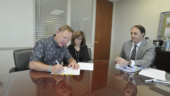 Quint and Rishy Studer sign the financing documents for their $52 million downtown apartment building project Monday afternoon as attorney Charles James of Clark Partington Hart looks on.