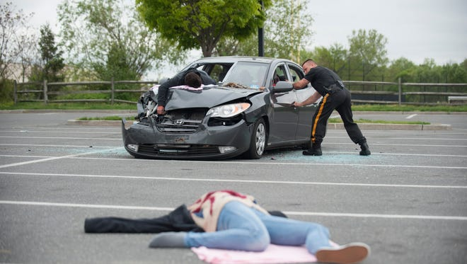 Members of the Gloucester City Police and Fire Departments stage a drunk driving car accident with students to illustrate the dangers of drunk driving as schools enter the prom and graduation season. Thursday, May 5, 2016.
