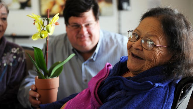 "Esther Ojeda has a big smile for volunteer John Christiansen from Alliance on Aging during Sunday's ""I Remember Mama"" event at Windsor Gardens in Salinas. Firefighters delivered hundreds of orchids to seniors in several locations on the morning of Mother's Day."