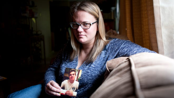 Julie Hartley, Ian Hartley's mother, poses for a portrait with a photo of him on Thursday, May 12 at her apartment in Charlotte. Since his death Hartley has raised over $2,000 for suicide prevention and is organizing a fundraiser for Aug. 6.