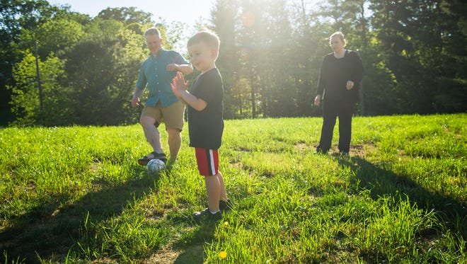 The Green family plays soccer in their front yard.