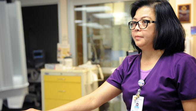 Mercedes Labindalaua checks patient records in the critical care unit at SVMH on Wednesday morning.