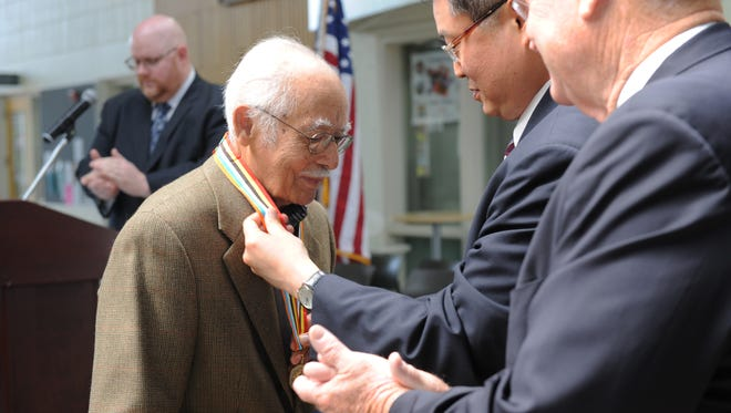 Korean War veteran Patrick McKenzie, 91, receives an Ambassador for Peace medal from Korean Consul General Shin Chae-Hyun at a ceremony Thursday at Hartnell College.
