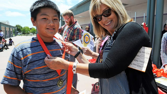 Creekside Elementary School Principal Marilyn Cline presents a Read to Me Project medal to student Anthony Leal for his literacy efforts at home with a younger sibling.