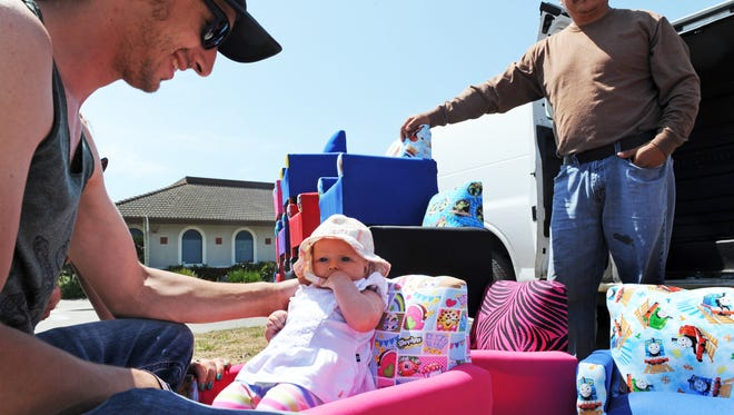 Kalika Sunrae, 3 months-old, gets a new baby chair from artisan Luis Hernandez, right, of Fresno.
