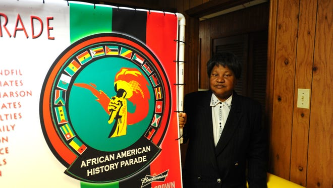 Jenelle Chargois holds a sign bearing the logo of the African American History Parade in Lafayette.