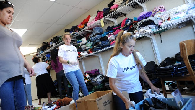 From left, volunteers Julia Vargas, Katherine Guthrie and Carmen Gonzalez help sort donated clothes at Tuesday's event.