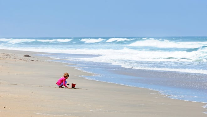 Immersed in experience, a little girl has this quiet stretch of beach near Moss Landing all to herself.