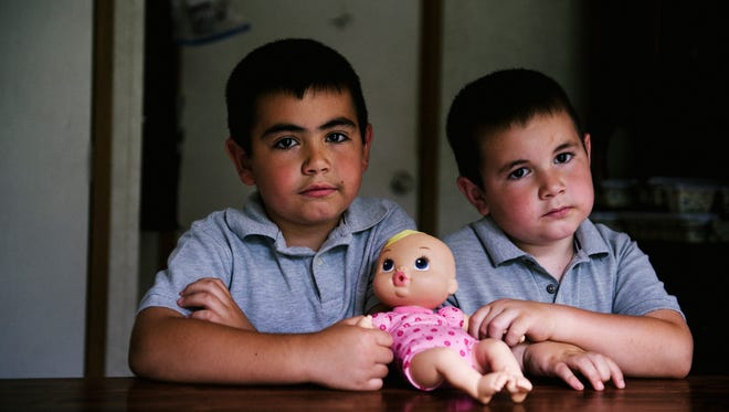 Brothers Jacob, 7, and Joseph Newman, 6, are photographed at the table where their two-year-old sister, Abagail, died due to accidental gunfire on October 26, 2015 in Hendersonville, NC.