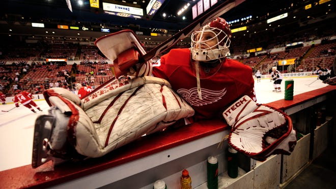 Goalie Chris Osgood stretches by the Red Wings bench in 2008.