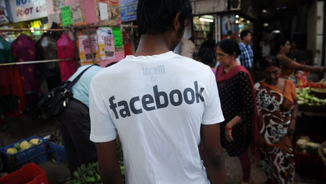 "(FILES) In this photograph taken on May 14, 2012, an Indian youth wearing a t-shirt with a Facebook logo walks through a vegetable market in Mumbai. India's top court on March 24, 2015, has struck down a controversial law that made posting ""offensive"" comments online a crime punishable by jail, after a long campaign by defenders of free speech. The Supreme Court said the 2009 amendment to India's Information Technology Act known as section 66A was unconstitutional and a restriction on freedom of speech.     AFP PHOTO/Indranil MUKHERJEE/FILESINDRANIL MUKHERJEE/AFP/Getty Images ORIG FILE ID: 539138228"