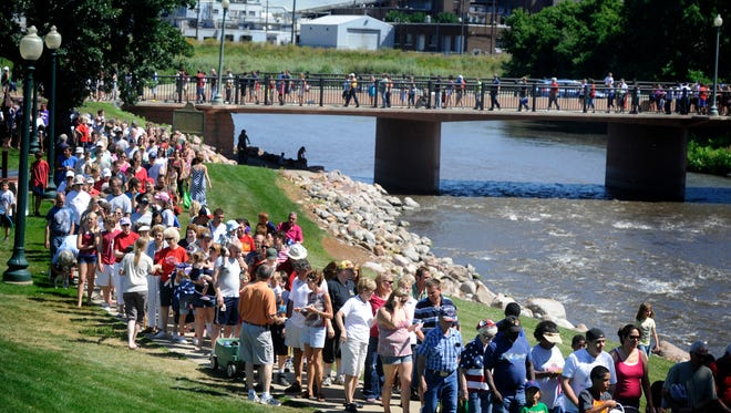 The food line for pork loin sandwiches snakes along and across the Big Sioux River on Monday at the annual Mayor's Fourth of July Parade and Picnic.(Jay Pickthorn/Argus Leader)