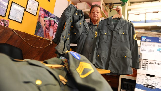 "Bob Cruz, Brand Inc. general manager, displays sets of vintage Army uniforms once worn by his older brother, Staff Sgt. Enrique ""Rick"" Cruz, in Tamuning on Wednesday, June 22. Staff Sgt. Cruz was awarded the Distinguish Service Cross for heroic actions he performed, in connection with military operations during the Vietnam War, on June 30, 1966."
