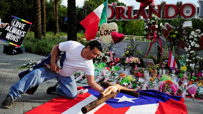 Jose Luis Morales prays near a crucifix after laying down the LGBT, Puerto Rican and American flags at a memorial in Orlando, Jun 15, 2016.