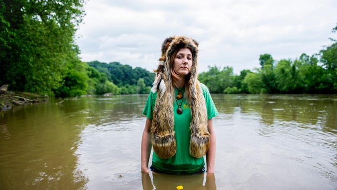Michelle Burleson is photographed in the French Broad River wearing her sister's SpiritHood. Burleson's sister, Alex King, was murdered with her girlfriend, Tatianna Diz, on Oct. 27, 2015. Their bodies were discovered in the French Broad a week later, a few feet from where Burleson is standing.