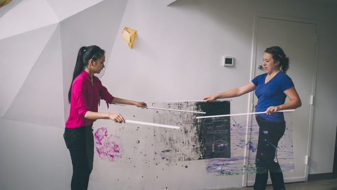 """Central High School student Nhan Phan working with mentor artist Adrienne Miller on an installation in the culminating exhibit of Louisville Visual Art's program """"The Future is Now."""""""