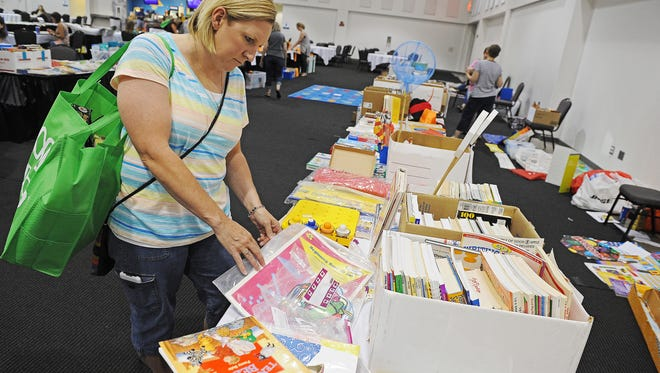 Kim Euchner, an early childhood education teacher at R.F. Pettigrew Elementary School, browses through items during the Sioux Falls Teacher Swap Meet Thursday, Aug. 11, 2016, at the Sioux Falls Convention Center in Sioux Falls.