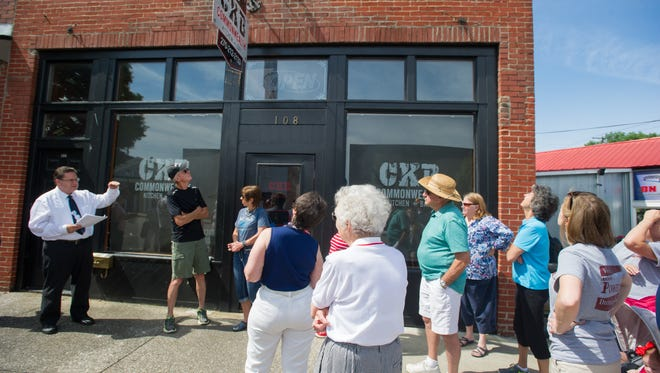Frank Nalley (left) talks about the history of the building that houses CKB Commonwealth Kitchen and Bar during a walking tour of the downtown restaurants in Henderson, Ky., Saturday morning, July 2, 2016.