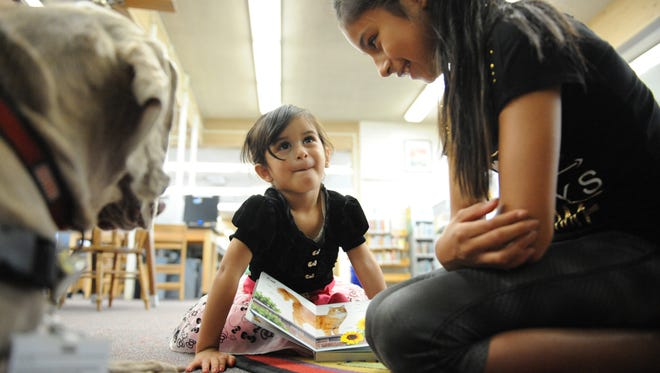 With her sister Isabella, 10, Penelope Virgen, 3, reads from a book of pets to Stormy Blue Bailey, a Weimaraner therapy dog at the Steinbeck Public Library in Salinas.