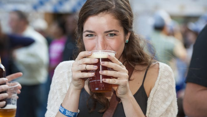 Mary Kate Gladstone of Xavier University tries the Oktoberfest beer from the Great Lakes Brewing Co.