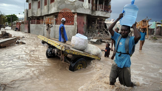 A man holding potable water walks in a street of the flooded city of Gonaives, north of Port Au Prince, on Sept. 08, 2008, after a hit from Hurricane Ike.