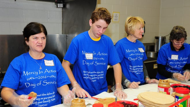 JoAnn Bahr, Grant Mathiesen and mom Kathy help make up to close to 500 sandwiches for St. Aloysius neighborhood services in Detroit as part of the service day held at St. Colette Church in Livonia.