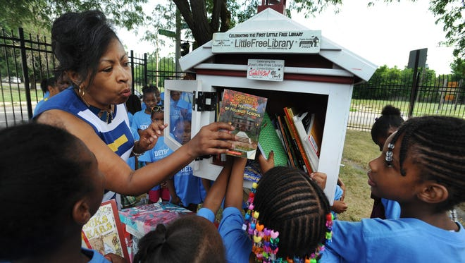 Marcus Garvey Academy Interim Principal Kim Lane helps her students select books from a Little Free Library in Detroit, Michigan on July 28, 2016.