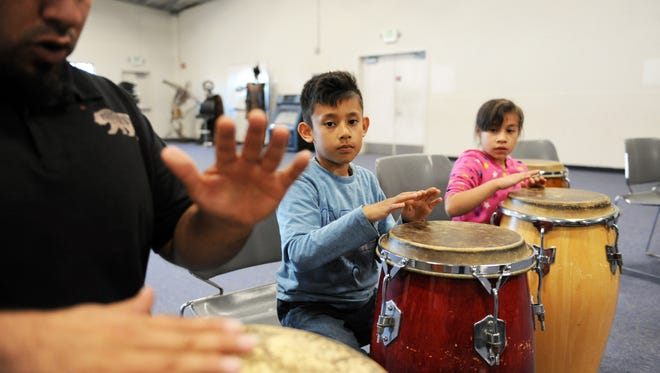 From right, Daniela Rios, 7, and her brother Eduardo, 6, follow drum instructor Javier Tamayo's lead in a world beat pattern at the Alisal Center for the Fine Arts.