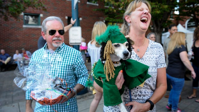 """Ramon and Amy Uribarri laugh as the show off  Jetta """" Scarlet O'Howl'A """", who won second place in the pet division of the costume contest,  Saturday October 28, 2016 at the 33rd annual PumpkinFest in Franklin, Tennessee."""