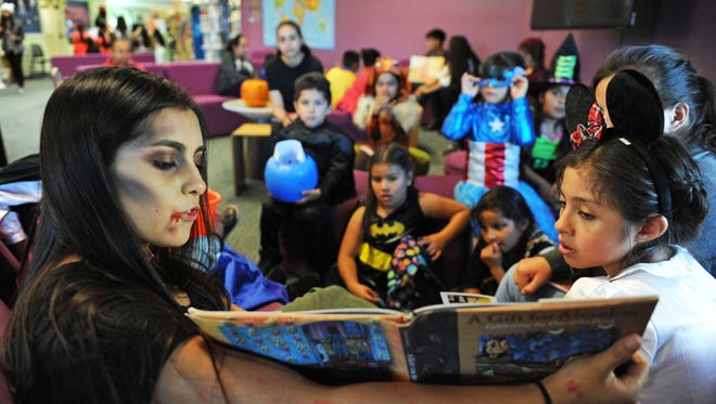 "Alisal High School senior (and zombie) Lesly Lopez reads ""A Gift for Abuelita"" to kids in Halloween costumes at the CŽésar Ch‡ávez Library in Salinas. Lopez is the vice-president of the Book Club at Alisal."