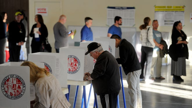 Voters fill out ballots at Grace Lutheran Church in Ventura on Tuesday. The polling place had a line of about 30 people.