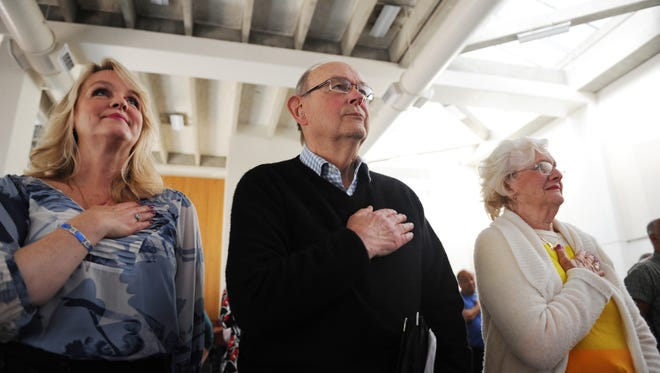 Veteran Ken Kelley and family members stand for the national anthem during a ceremony honoring veterans held at Hartnell College on Thursday.