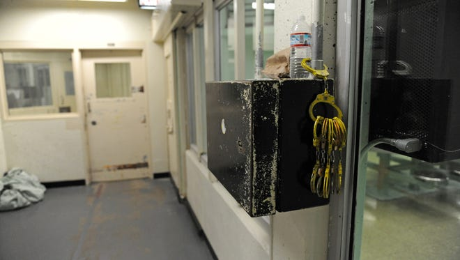 Handcuffs hang from a pipe outside a cell block door in the men's section of the Monterey County Jail in Salinas, CA.