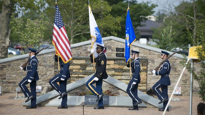 An Honor Guard marches past the U.S. Air Force Air Advisor Memorial aT Joint Base McGuire-Dix-Lakehurst.