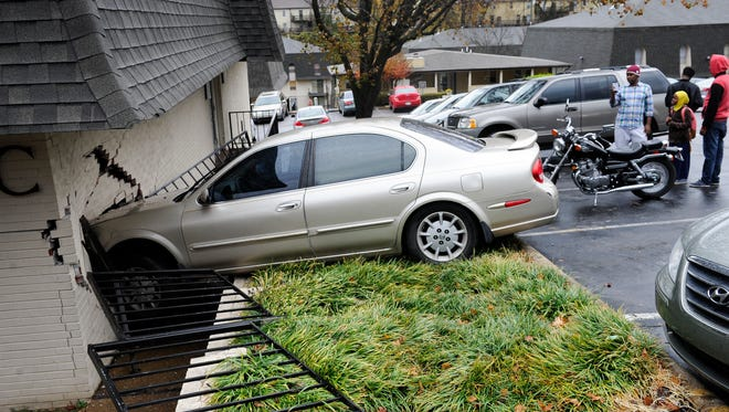 The owner and driver of the 2002 Nissan Maxima take pictures of their vehicle that crashed into an apartment building at on Vultee Boulevard on the morning of Wednesday, Nov.30, 2016,  in Nashville, Tenn.