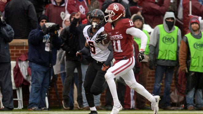 Oklahoma wide receiver Dede Westbrook runs for a touchdown while pursued by Oklahoma State cornerback Ashton Lampkin.