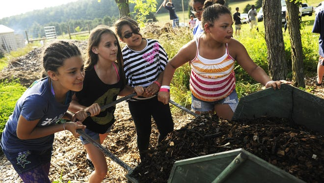 Girls from the Boys & Girls Club push a wheelbarrow filled with mulch at the Project Grows farm Thursday, June 20, 2013, in Verona.