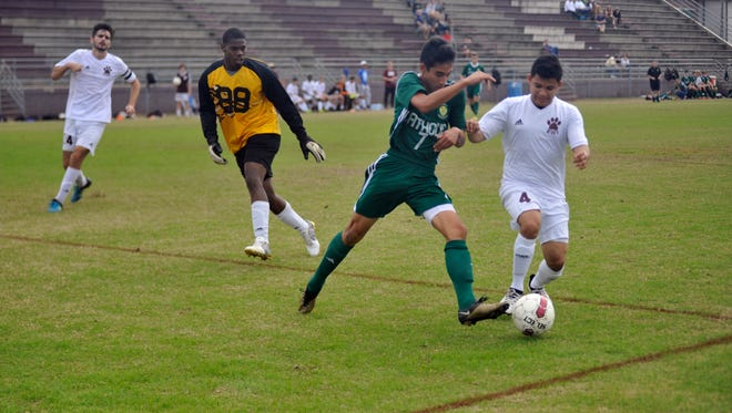 Catholic freshman Tyler Ryals (left) challenges Pensacola High's Mainor Peralta (right) after dribbling around goalkeeper Walter Granderson (yellow jersey) on Dec. 17, 2016.