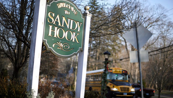In this Dec. 4, 2013 file photo, a school bus drives past a lamppost decorated for the holidays, and a sign reading Welcome to Sandy Hook, in Newtown, Conn. (AP Photo/Jessica Hill, File)